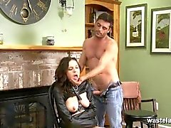 Restrained brunette in leather straight jacket sucks her Masters cock